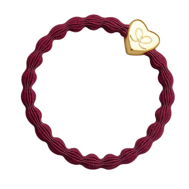 A gold heart charm on a burgundy hairband, bangle band hair bands and bracelets at byEloise.