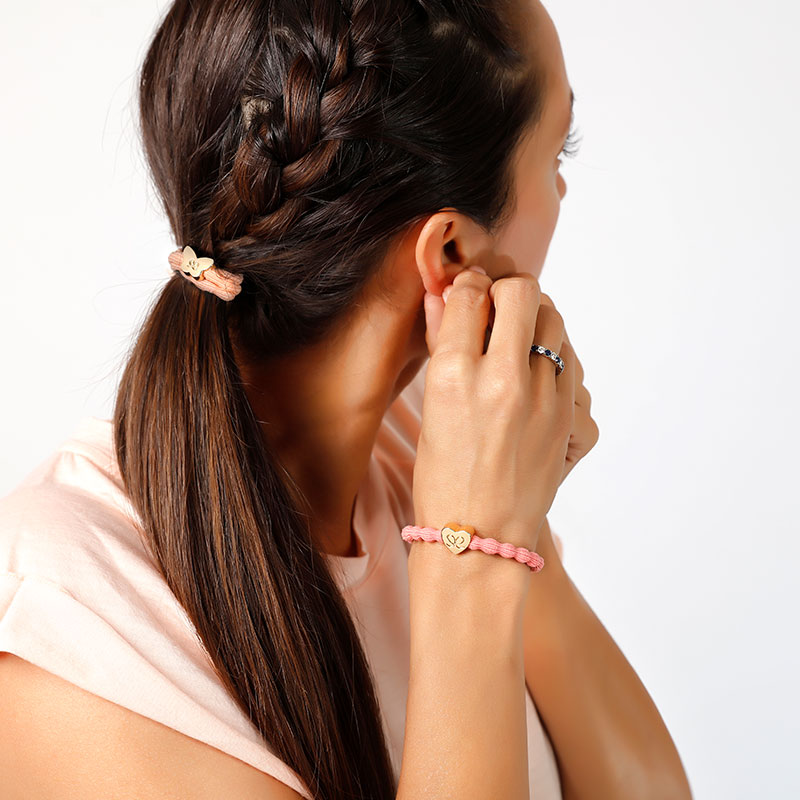 A woman, hair braided with a bangle band hair tie and wrist adorned by bangle band bracelet.