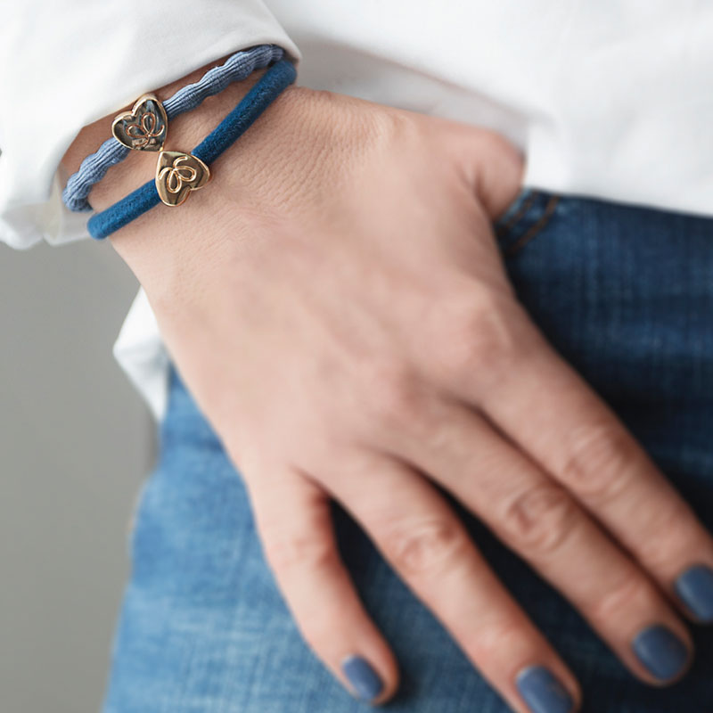 The gold heart charm on dove blue bangle band worn on the wrist.