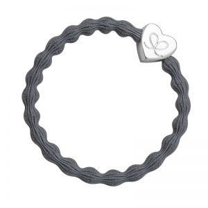 A silver heart charm on a storm grey hairband, part of the collection of fashionable hair bands from byEloise.