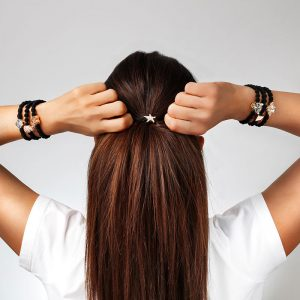 Rear view of a woman positioning a byEloise starfish bangle band in luxuriant auburn hair.