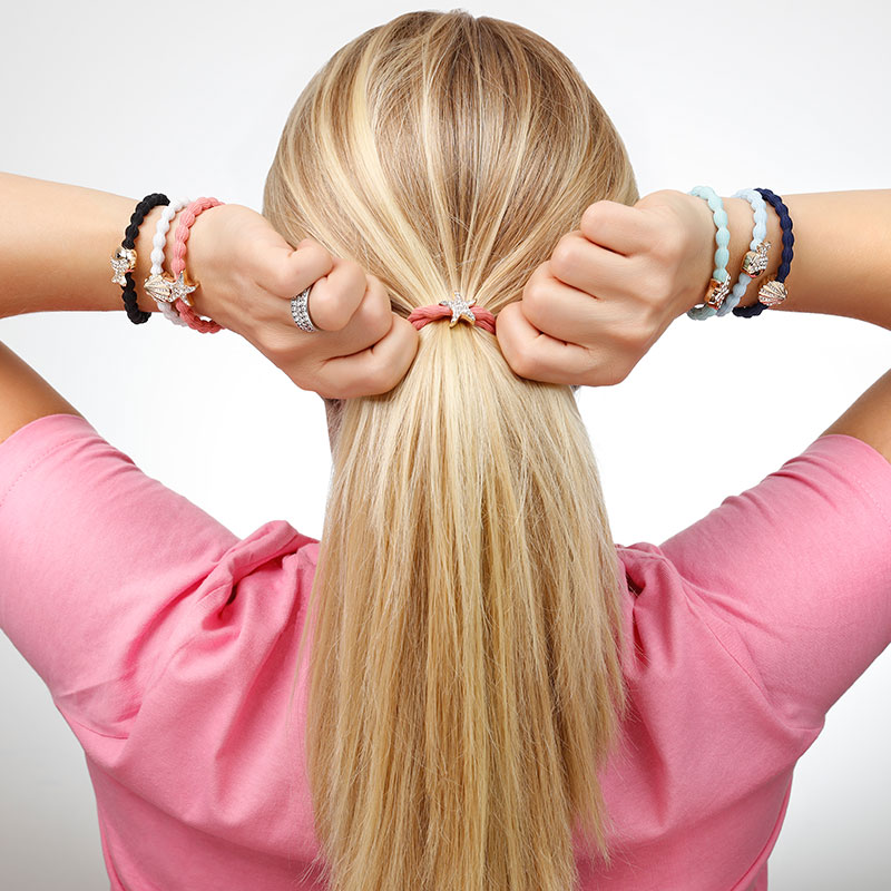 Woman wearing a coral top and positioning a byEloise London bangle band in luxuriant blonde hair.