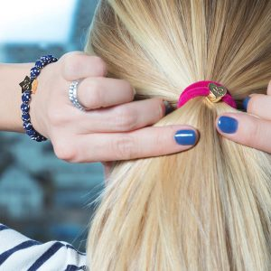 A woman with a bangle band gold heart tie in her hair and bangle bands gold star charm bracelet on her wrist.