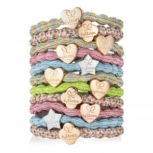 A stacked tower of byEloise bangle bands with gold heart and silver star charms.