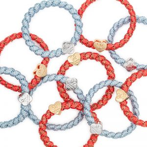Several woven byEloise London bangle bands, fashionable hair band bracelets, with gold and silver charms.