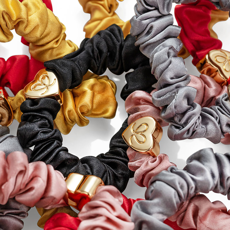 Close up of several byEloise London silk scrunchie bangle bands with gold heart charms.