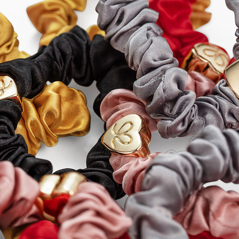 Detail of byEloise silk scrunchie bangle bands with gold heart charms.