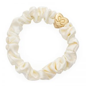 A gold heart charm on a cream silk scrunchie, part of the bangle bands hair band bracelets collection from byEloise.