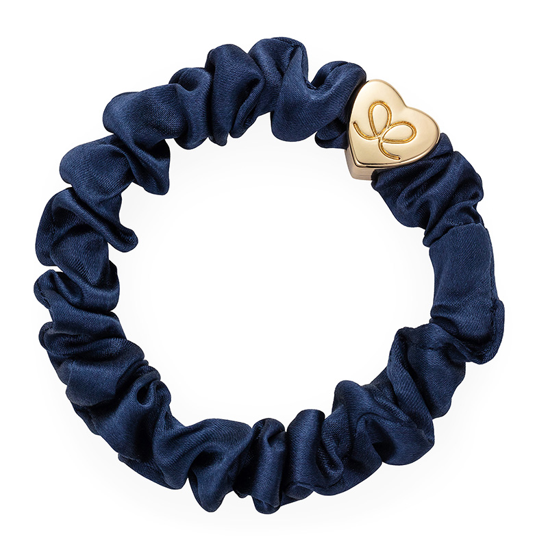 A navy silk scrunchie with a gold heart charm, one of the fashionable hair bands from byEloise London.