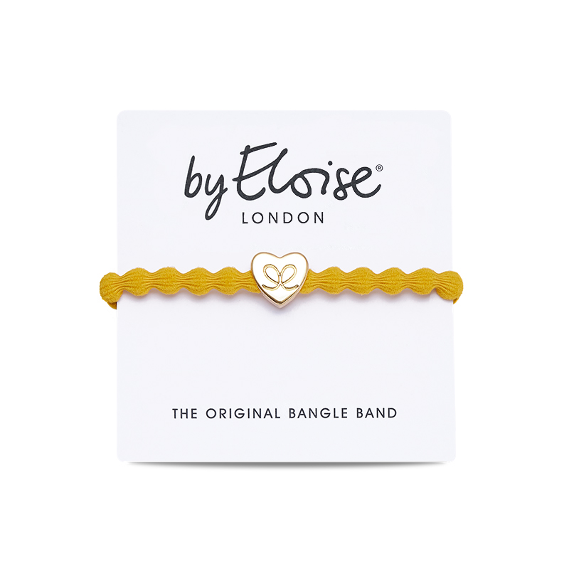 A yellow bangle band with a gold heart charm on a byEloise London display card.