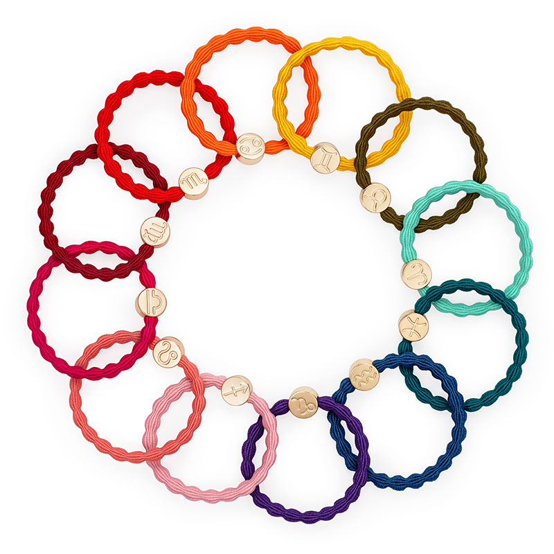 Twelve byEloise zodiac hairband bracelets, each with a different sign of the zodiac, arranged in a circle.