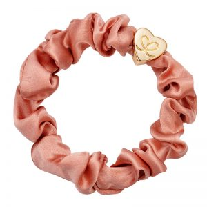 Gold heart charm byEloise bangle bands on an apricot blush silk scrunchie against a white background.