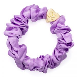A gold heart charm on a lilac silk scrunchie Lilac, part of a range of stylish hair accessories from byEloise.