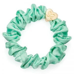 A gold heart charm on a mint silk scrunchie bangle band, part of a range of chic hair accessories from byEloise.